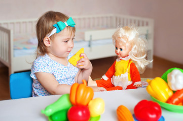 Little girl playing indoors at home or kindergarten. Adorable smiling little child cutting plastic vegetables with knife and feeding her doll. Healthy lifestyle for kids.