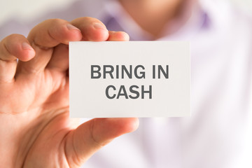 Businessman holding a card with BRING IN CASH message