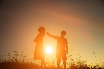 a silhouette of a man and woman holding hands with each other, walking together