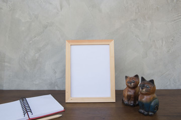 photo Frame on a wooden table and book and toy cat on Gray wall background .