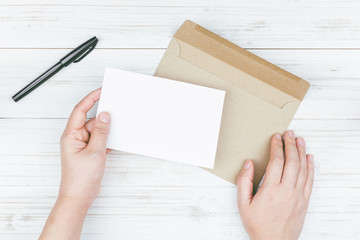 Hand hold a envelope and paper on the wooden background
