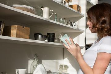 Female taking box from shelf