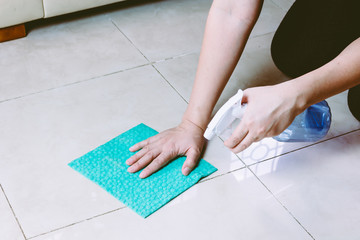 Woman  with cloth and  spray cleaning floor at home
