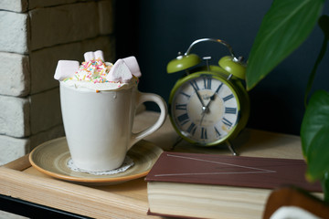 Breakfast table with cup of  hot white chocolate, whipped cream, marshmallows,alarm watch and book.Breakfast time.