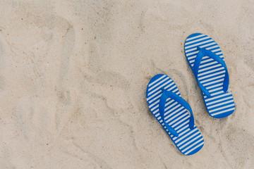 Blue flipflop  on beach sand