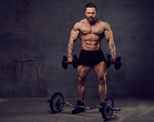 Muscular, bearded male doing biceps workouts with dumbbells.