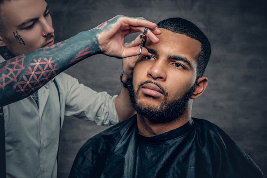 Tattooed barber makes haircut to a Black bearded male.