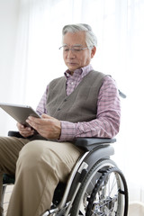 Senior man in wheelchair looking at tablet PC
