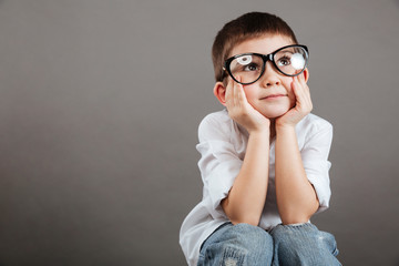 Thoughtful little boy in glasses sitting and thinking