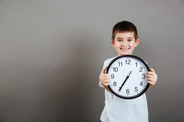 Cheerful little boy standing and holding clock