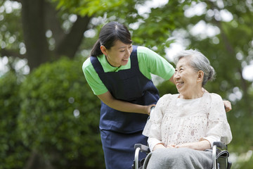 Healthcare worker pushing senior woman in wheelchair, Tokyo Prefecture, Honshu, Japan