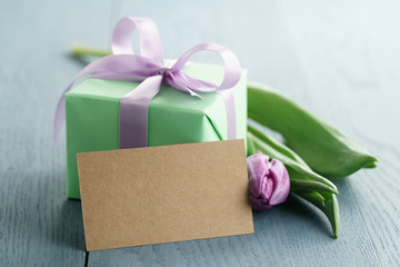 green gift box with purple bow and tulip on blue wood background with empty greeting card, romantic photo