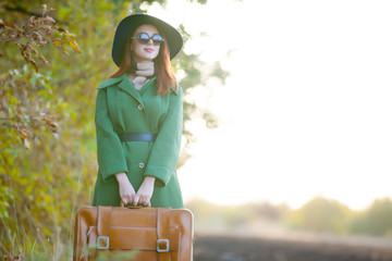 beautiful young woman with brown suitcase near trees on the field background