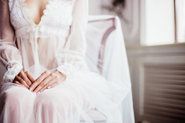 beautiful girl in white transparent boudoir gown of tulle and lace sitting on a chair hands close-up
