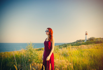 beautiful young woman standing in front of wonderful sea and lighthouse background
