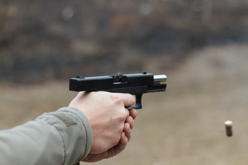 Shooting from a pistol. Reloading the gun. The man is aiming at the target. Shooting range. Man firing usp pistol at target in outdoor shooting range