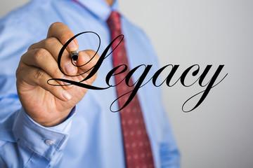 Businessman writing Legacy word on virtual screen