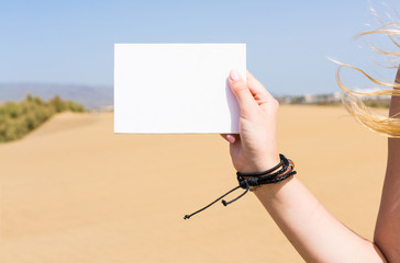 Blank postcard in a girl's hand against a sandy desert background