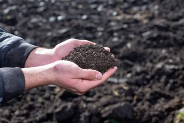 Farmer holding soil in hands in field
