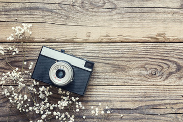 Vintage camera with small white flowers on old wooden background. Copy space for text.