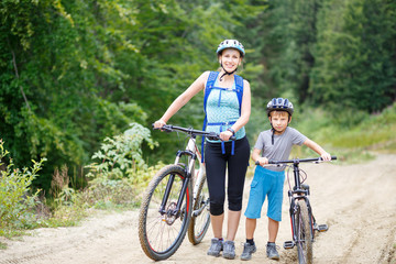 Young woman with her son standing with bikes in mountain forest