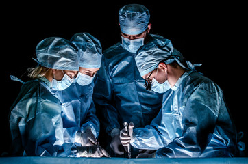The doctor makes sternotomy during a thoracic operation. Doctors are dressed in blue surgical suits, on their faces they have medical masks, and on their heads surgical caps. Wall mural