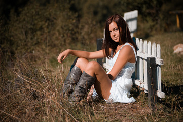 Portrait of a beautiful girl in a white dress and cowboy boots