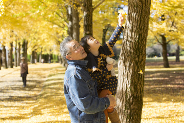 Grandfather and granddaughter looking at Ginkgo tree in autumn