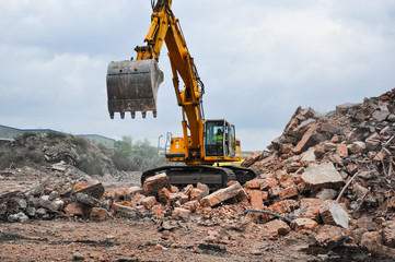 Excavator working at the demolition of an old industrial buildin