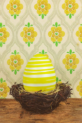 Yellow dyed big easter egg in a bird nest on a wooden table