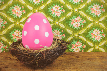 Pink dyed big easter egg in a bird nest on a wooden table