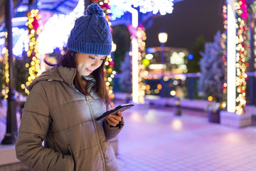 Woman sending sms on cellphone in Yokohama night