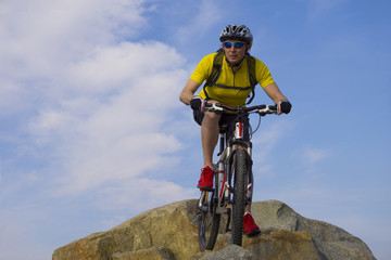 Downhill rider, in yellow t-shirt and red sneakers, on mountain bike with cloudy sky background