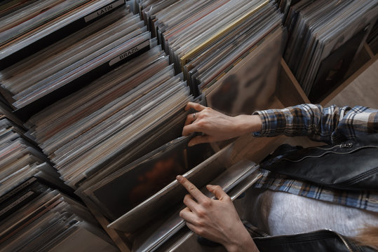 female hands browsing vinyl records in a store
