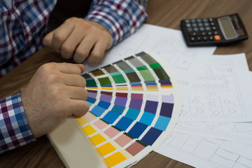 Man architect draws a house plan with color palette for furniture, work tools.