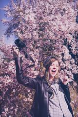 Preciosa chica joven, hipster, haciendo fotos con su cámara en primavera, cerca de un árbol en flor