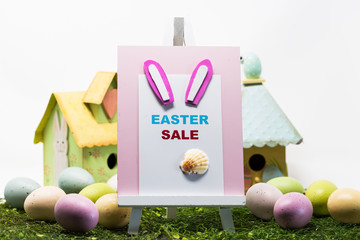 Colorful Easter eggs and sale sign on the pink board isolated on white background