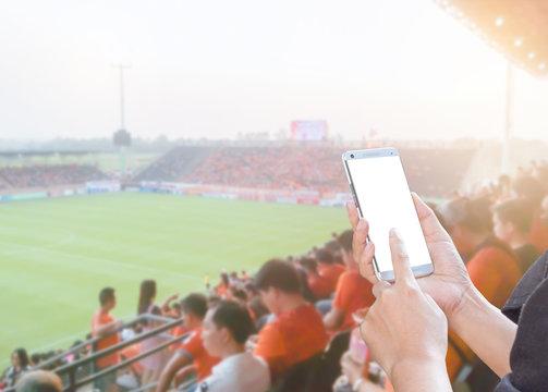 Woman hands using mobile smartphone on Football stadium