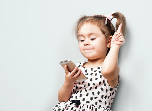 Cute little girl holds teleprone and notes to empty space for your text