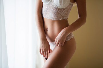 Slim perfect female body. Young attractive woman in white lingerie showing very flat belly