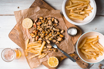 Fried potatoes, mussels, lemon on parchment and beer