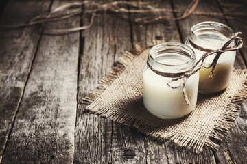 Fresh cow milk or cream in glass bottles, rustic style, vintage wood background