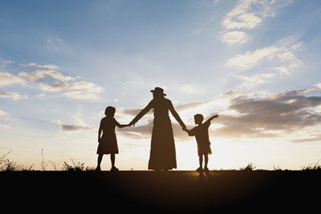 Silhouette of mother and kids holding hands at sunset