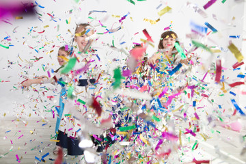 Happy children having fun celebrating birthday. Group of children throws up multi-colored tinsel and confetti. Positive emotions.