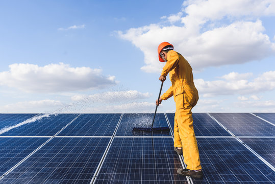 Worker cleaning solar panels