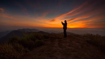 Silhouette of a man taking picture in the sunset