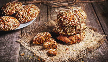 Homemade cookies with sesame, dark wood background, selective focus