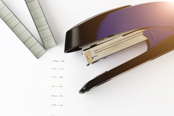 Stapler with staples on white paper