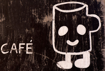 Old wooden vintage wall with an inscription cafe and big white smiley  coffee cup