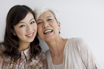 Portrait of mature woman and young woman, smiling, white background
